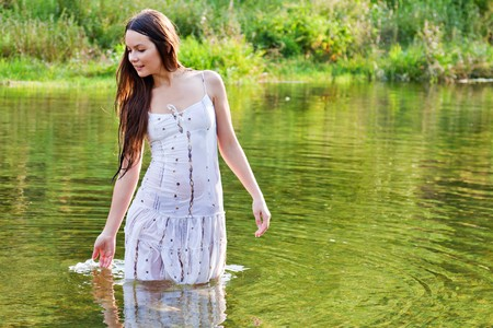 Young woman in white dress in a river photo