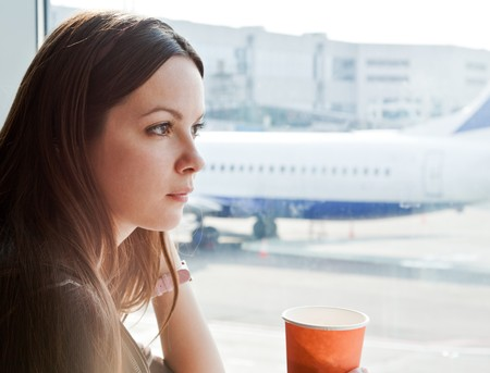 arrival departure board: Young woman is drinking coffee in airport Stock Photo