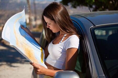 Stand de la joven mujer cerca del coche y la mirada en el mapa