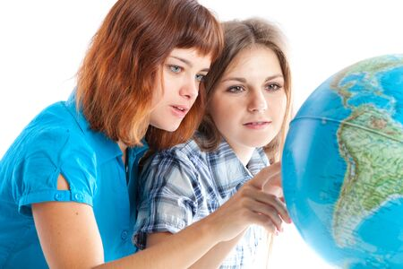 Two teen-girls are looking at globe. Isolated on white background Stock Photo - 7873910