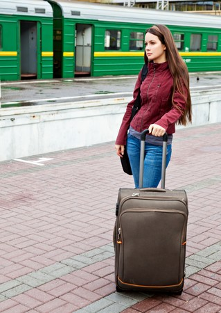 Beautiful young woman with luggage is waiting a train photo