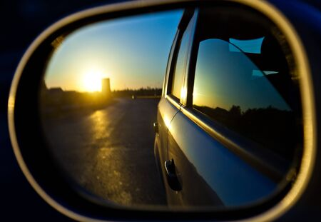 A sunset in the rearview mirror of car as a races down the road. Window of car is opened photo
