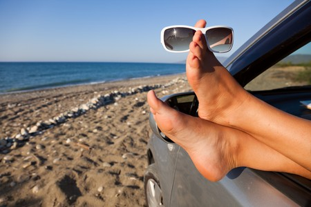 Womans legs dangling out a car window parked at the beach photo