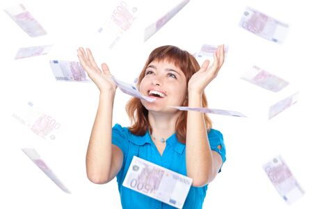 Banknotes of 500 euro are falling on red-haired girl. Isolated on white background photo