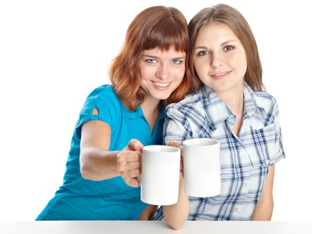 Two teen-girls are drinking tea. Isolated on white background photo