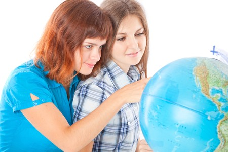 Two teen-girls are looking at globe. Isolated on white background Stock Photo - 8005323