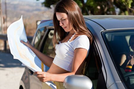 Young woman stand near the car and look on map photo