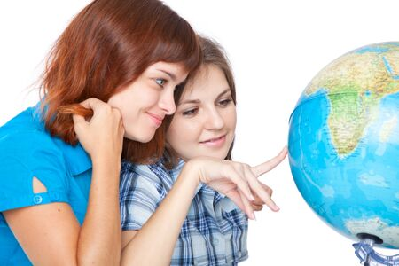 Two teen-girls are looking at globe. Isolated on white background Stock Photo - 8218861