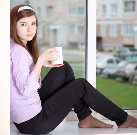 adolescence: a girl with a cup is sitting on the window-sill