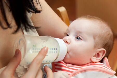 Jonge moeder voedt haar baby van een bottleat huis