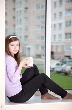a girl with a cup is sitting on the window-sill photo