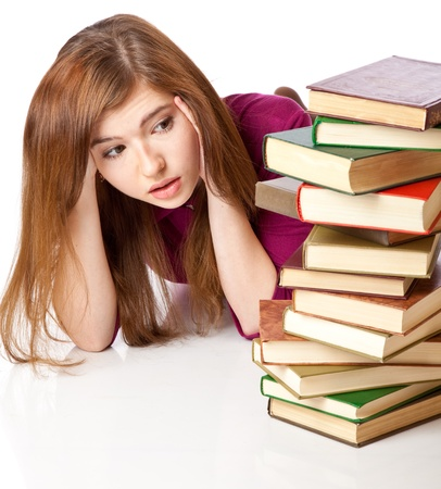 a scared girl is looking to the pile of books. isolated on white background Stock Photo - 8303282