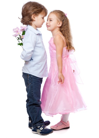 sidewards: a boy with a bunch of flowers is standing near a beautiful girl. isolated on a white background Stock Photo
