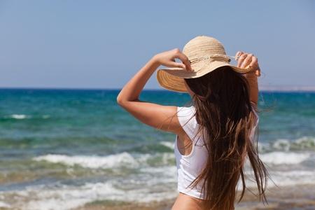 een vrouw in een motor kap is kijken naar de zee
