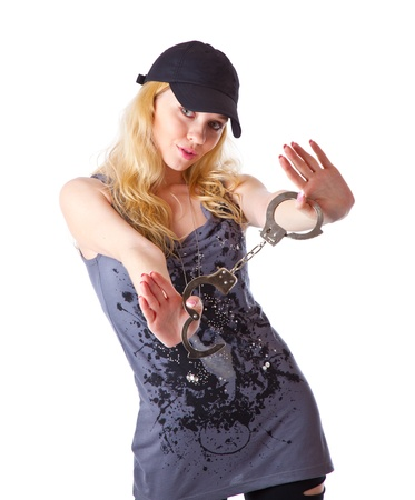 a girl in a cap with handcuffs in hands. isolated on a white background photo