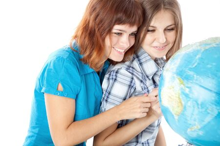 Two teen-girls are looking at globe. Isolated on white background Stock Photo - 8568496