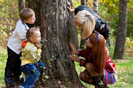 Two mothers are playing hide-and-seek with their children
