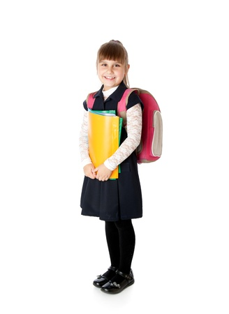 Schoolgirl is standing with folders in hands. Isolated on white Standard-Bild