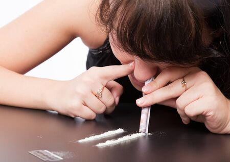smack: a girl is sniffing cocaine (imitation). isolated on a white background