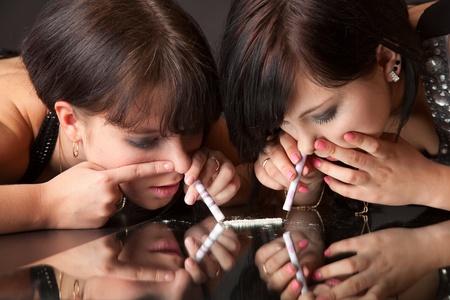 meisjes zijn het snuiven van cocaïne (imitatie). geïsoleerd op een zwarte achtergrond