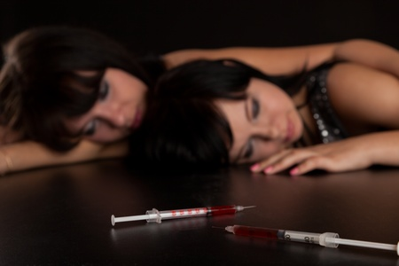 opiate: two girls died because of drugs (imitation). isolated on a black background