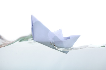 a paper boat in pure transparent water. isolated on a white background