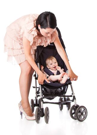 buggy: a young woman is standing near her child in a pram. isolated on a white background