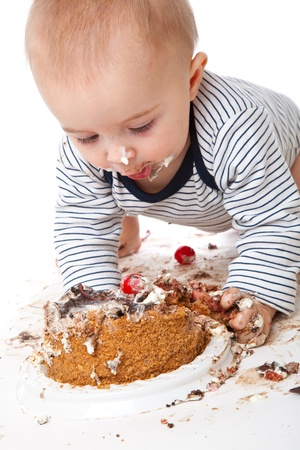 a funny baby is eating a tasty cake. isolated on a white background photo