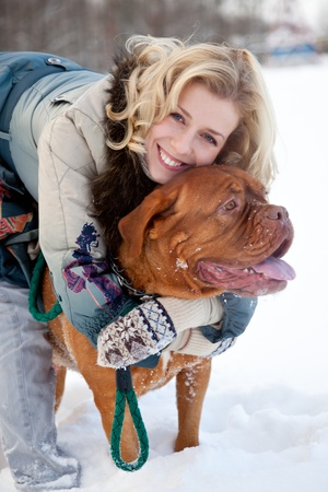 a smiling beautiful woman with a dog are in the winter park photo