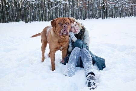 a beautiful smiling woman is sitting near her dog in the winter park photo