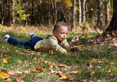 a smiling girl is laying on a grass in the forest photo