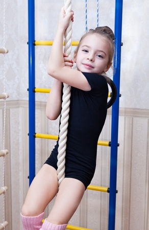 little girl smiling: a beautiful smiling girl climbs on a rope Stock Photo