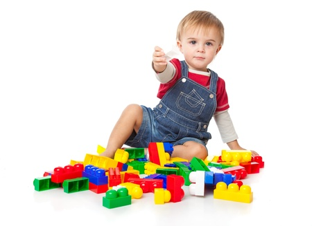 plastic bricks: a funny boy is playing with plastic bricks. isolated on a white background Stock Photo