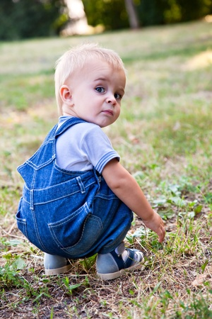 searching for: a funny boy is looking for something in the grass Stock Photo