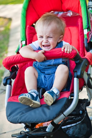 a resentful baby is crying in the pram photo