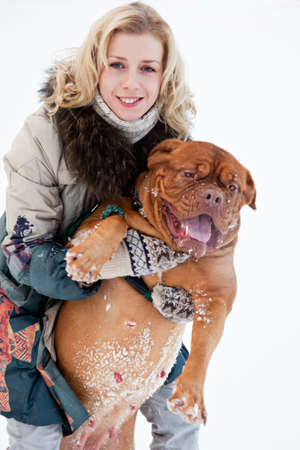 a smiling woman is sitting at the snow with her dog Stock Photo - 8757441