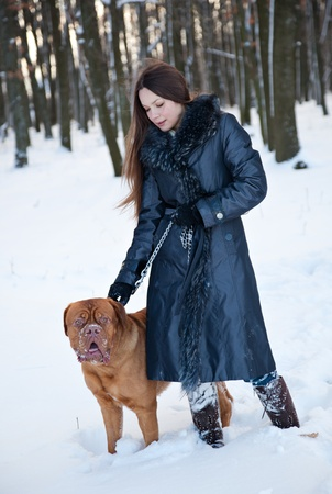 a beautiful woman is walking in the park with her dog photo