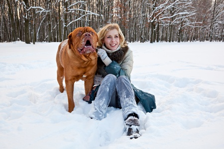 a smiling woman is sitting at the snow with her dog photo