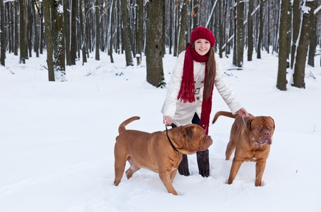 a beautiful smiling woman is walking in the park with her dogs photo