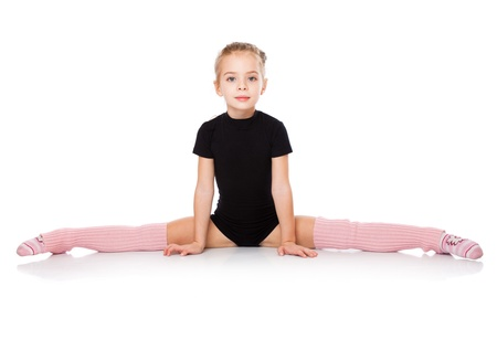 female gymnast: a beautiful girl sits on a splits. isolated on a white background