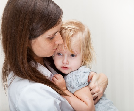 child protection: a mother is holding tight a sick girl.  Stock Photo