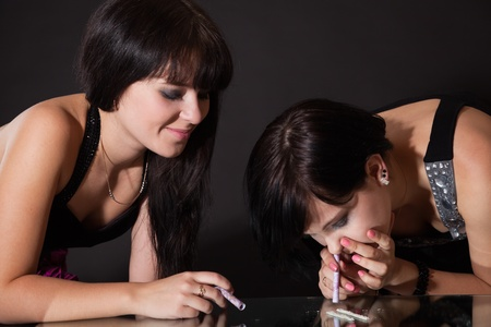 girls are sniffing cocaine (imitation). isolated on a black background Stock Photo