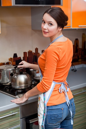 gas stove: a beautiful young woman is putting a kettle