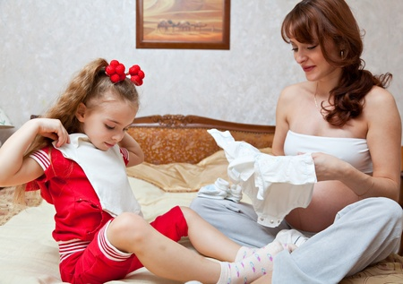 A daughter and her mother measure the childrens clothes photo