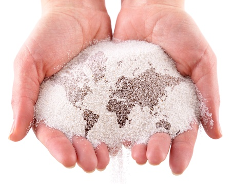 Sand with map of the world in the hands. Isolated on a white background Standard-Bild