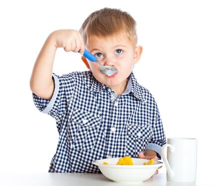 cereals: Un ni�o es comer cereales desde un taz�n. Aislado en un fondo blanco Foto de archivo