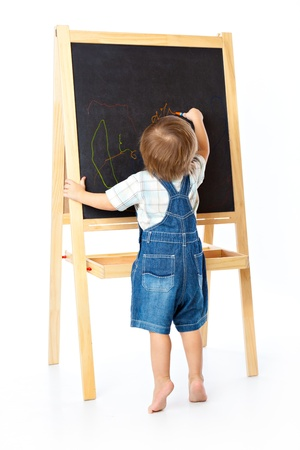 children in class: A boy is drawing on a blackboard Stock Photo