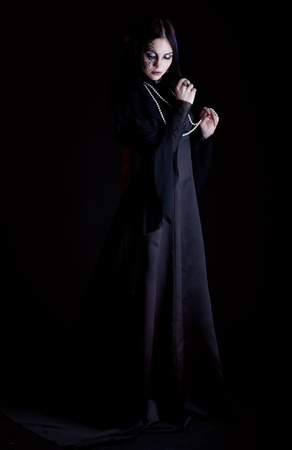 A goth-girl on black background is holding a cross