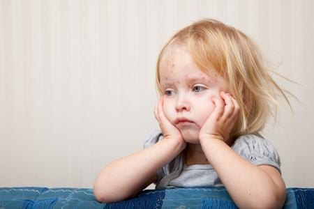 Une petite fille malade est assis près du lit Banque d'images - 9445126
