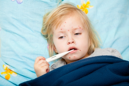 child protection: a sick cute girl is measuring the temperature